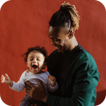 Young black father holding his toddler who is laughing | Finsure UK