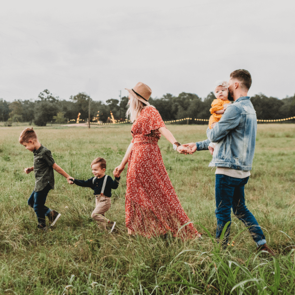 Mother, father and three children walking across a field holding hands | Finsure UK