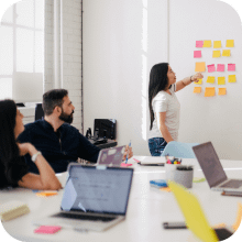 The head of marketing giving a presentation in front of her colleagues | Finsure UK