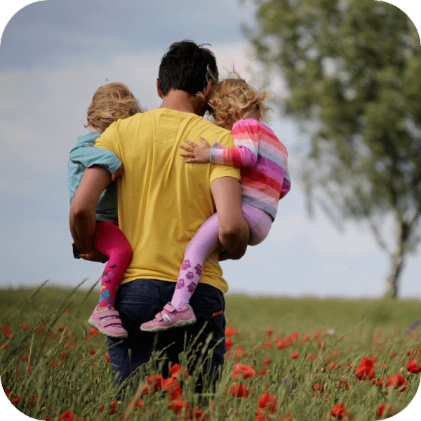 A father walking through a poppy field holding his two daughters either side | Finsure UK