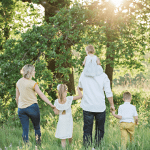 A family of five walking away into the woods on a sunny day | Finsure UK