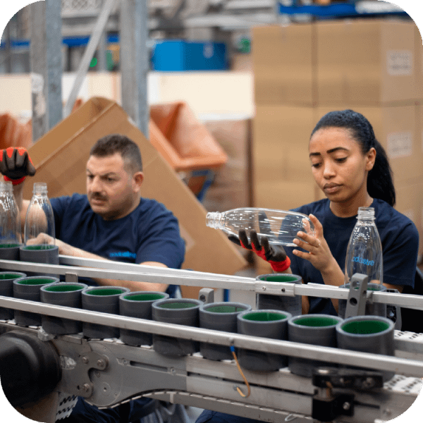 A man and a woman working in a plastic bottle factory inspecting the bottles | Finsure UK