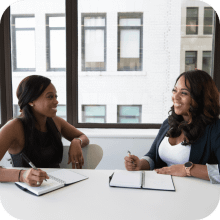 Two black female business owners having a discussion and taking notes about their reason for a secured business loan   Finsure UK