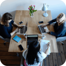 Three female business owners sat around a table on their laptops | Finsure UK