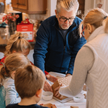 Grandparents with three grandchildren making a gingerbread house | Finsure UK