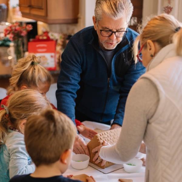 Grandparents with three grandchildren making a gingerbread house | Finsure UK