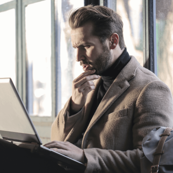 Male business owner looking intently at his laptop exploring bridging loans | Finsure UK